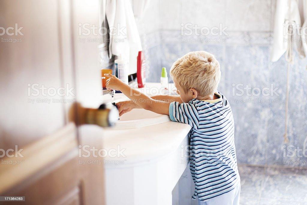 Little boy washing hands in bathroom stock photo