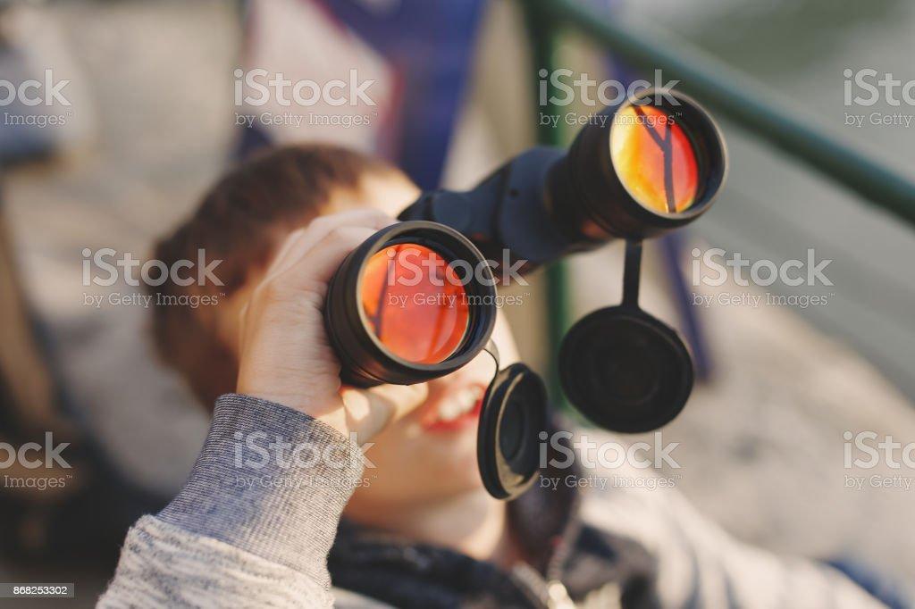 Little boy watching airplane on sky by binoculars stock photo