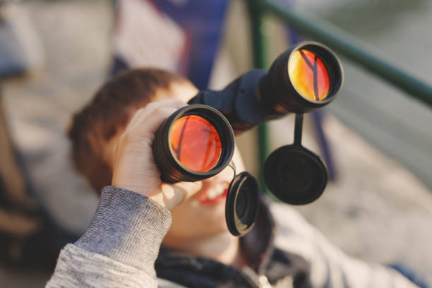 little boy watching airplane on sky by binoculars - airshow stock photos and pictures