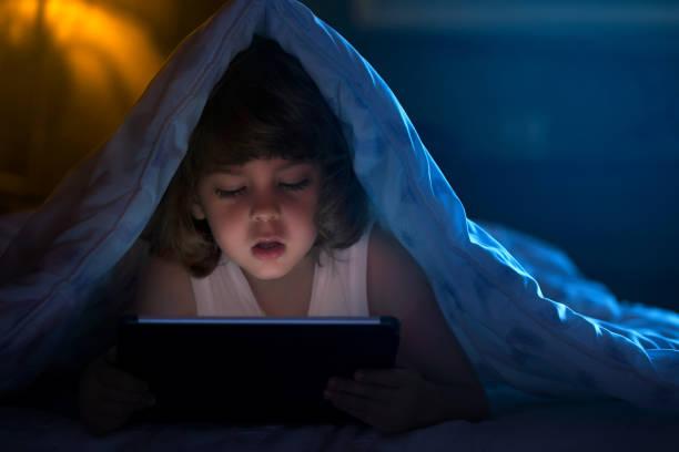 Little boy watching cartoons at night stock photo