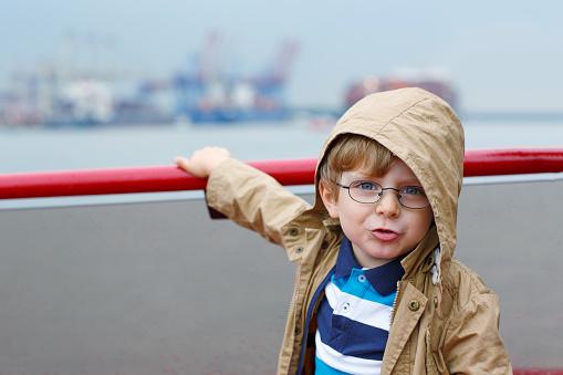 Little boy watching ships on a ferry.