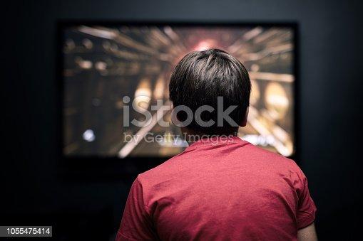 Facing back caucasian little boy playing video game on television. Television and video game addiction.
