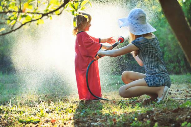 Kleiner Junge, der mit seiner Mutter im Garten wässert – Foto