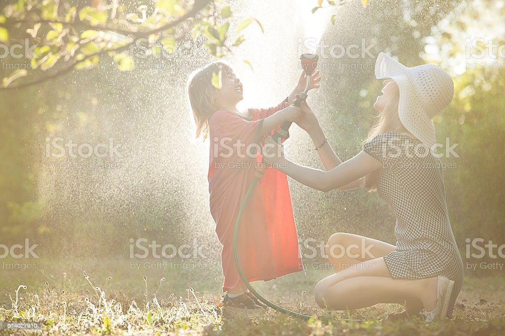 Little boy watering with his mother in garden stock photo