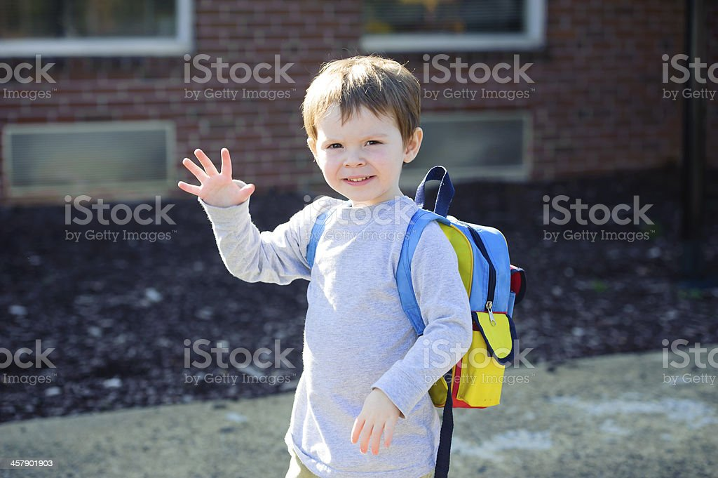 Little boy waving on first day of school wearing school bag stock photo