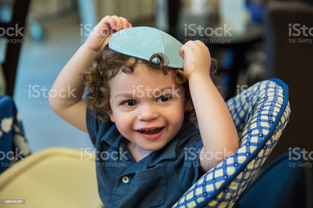 Little boy wearing a yarmulke sits in highchair stock photo