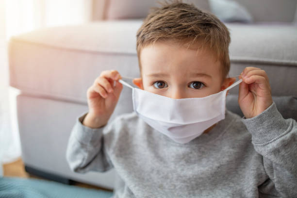 Little boy wearing anti virus mask staying at home. Young child wearing a respiratory mask as a prevention against the Coronavirus Covid-19. Little boy wearing anti virus mask staying at home. Protection against flu and virus infection pollution mask stock pictures, royalty-free photos & images