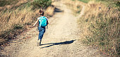 Little boy wearing backpack running on a dirt road on a sunny late summer day. He's running to school, or hiking or just running for fun.