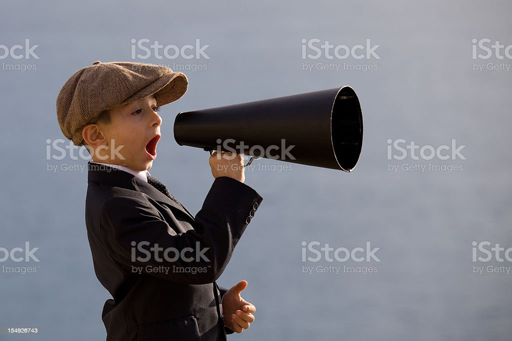 Little Boy Wearing Flat Cap Shouting On Old Fashioned Megaphone stock photo