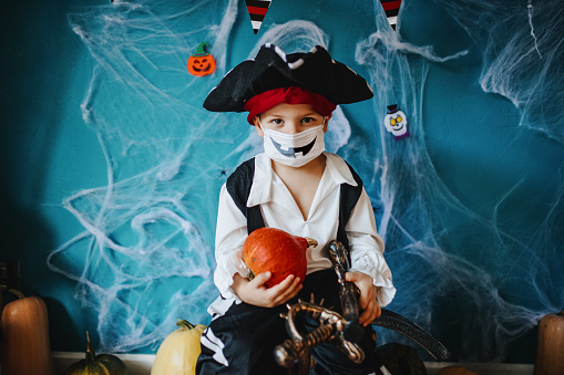 Little boy wearing Halloween costume and protective face mask during Covid-19 pandemic