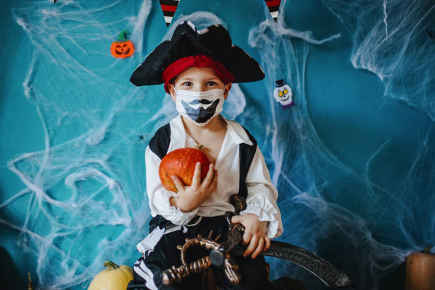 covid-19パンデミック中にハロウィーンの衣装と保護フェイスマスクを身に着けている小さな男の子 - halloween ストックフォトと画像