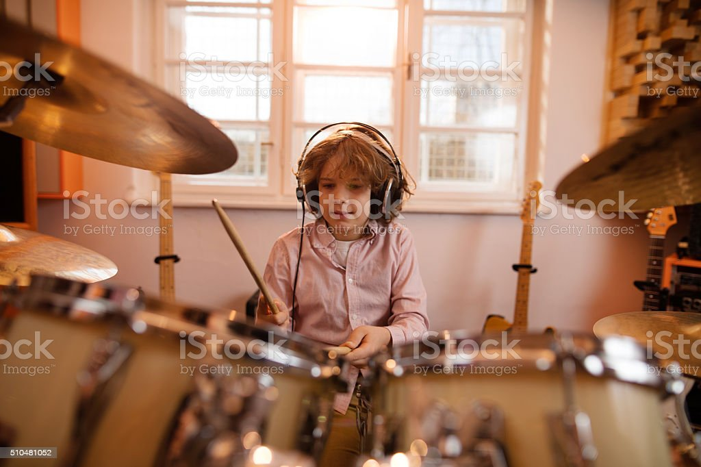 Little boy wearing headphones and playing drums. stock photo