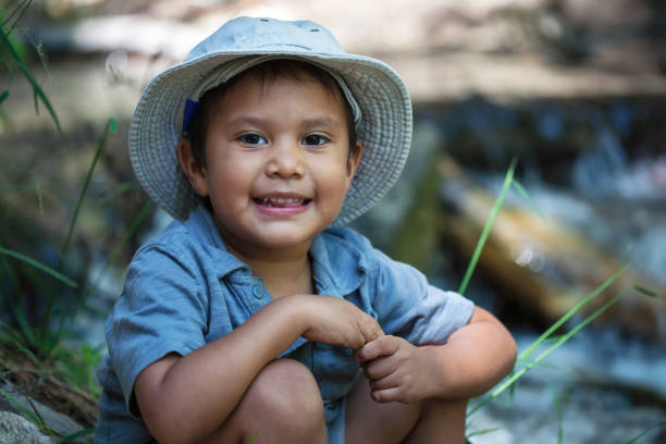 A little boy wearing his fishing hat, sitting next to the the rivers edge during summer. stock photo
