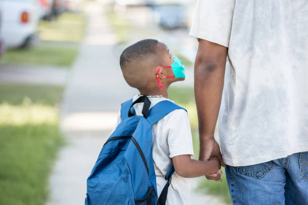 Little boy wearing mask and backpack looks up at father while they walk to school together stock photo