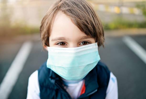 Little boy wearing medical mask during Coronavirus COVID-19 pandemic stock photo
