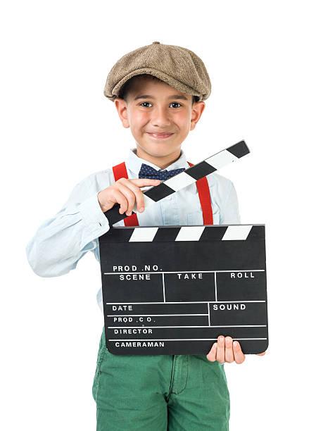 kleiner junge trägt zeitungsjungen-mütze posieren mit film schiefer - klappe hut stock-fotos und bilder