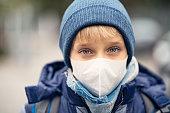 Portrait of a little boy wearing pollution mask. \nNikon