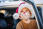 istock Little boy wearing protective face mask and Santa hat in car on Christmas 1283898409