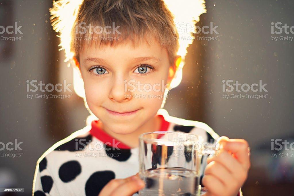 Petit garçon portant pyjama matin boire un verre d'eau. - Photo