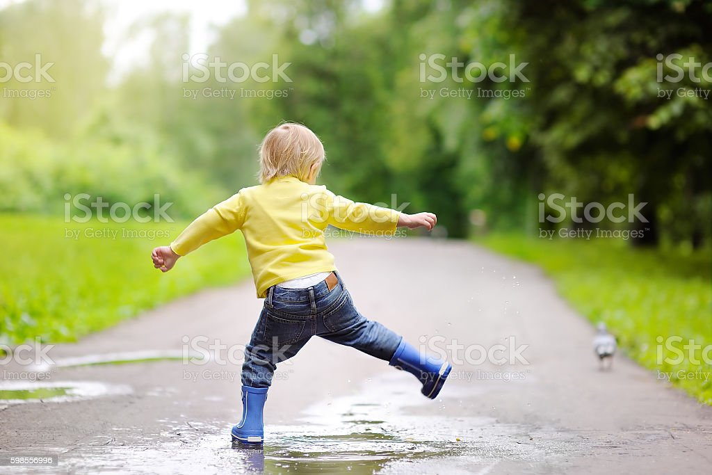 Little boy wearing rain boots jumping in pool of water stock photo