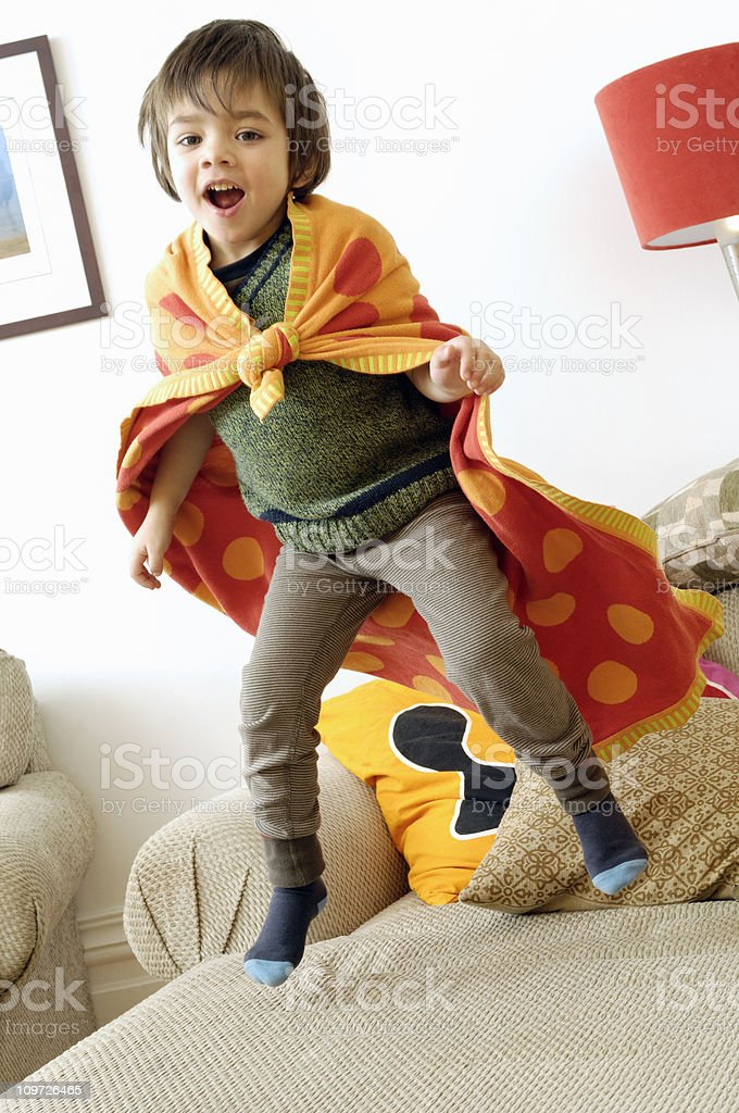 Little Boy Wearing Towel as Cape and Jumping on Couch royalty-free stock photo