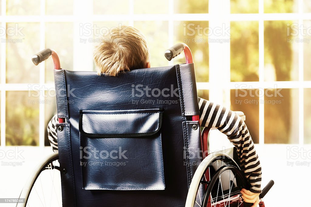 Little boy wheels his wheelchair towards sunny window stock photo