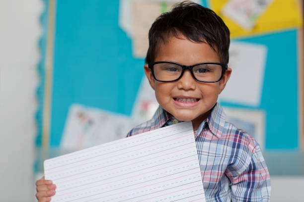 A little boy with a cute smile who is holding up a writting guide board and is wearing reading glasses with a preppy style shirt. stock photo