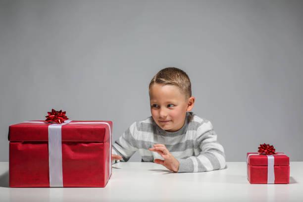 Kleiner Junge mit ein kleines und ein großes Geschenk – Foto