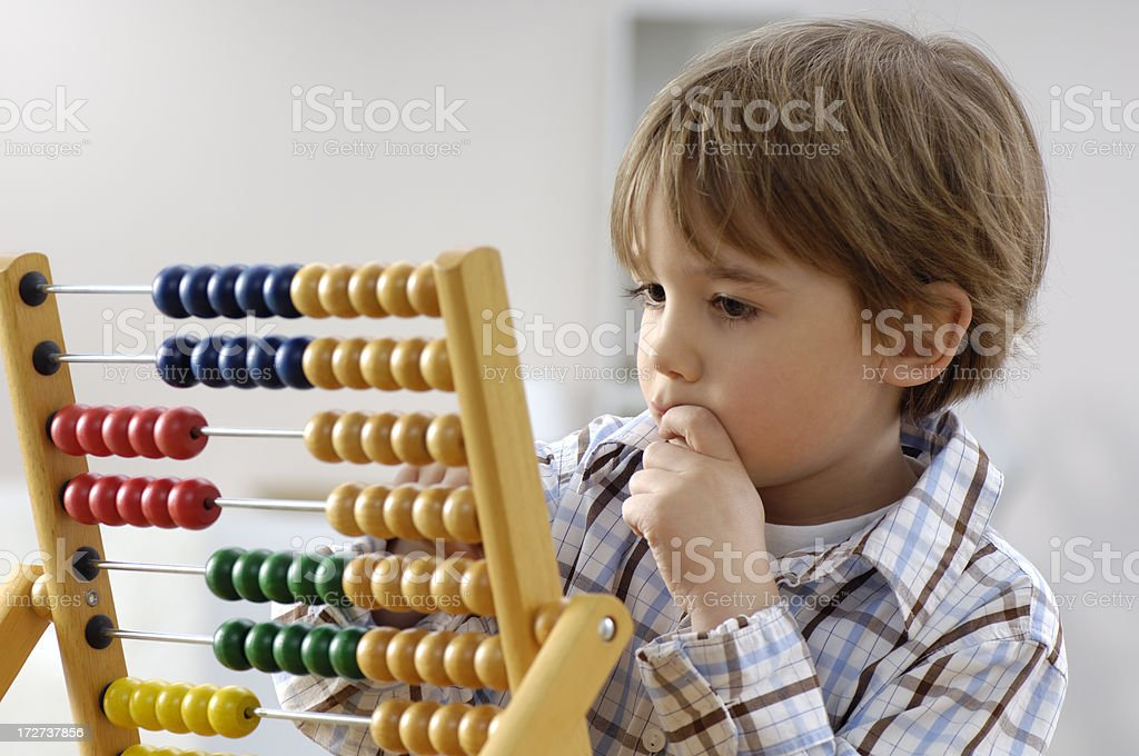 Little boy with abacus Cute little boy thinking.Please see some similar pictures from my portfolio: 6-7 Years Stock Photo