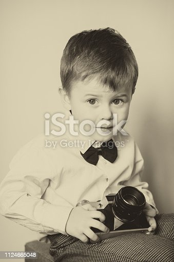 Little boy with aged retro camera. Young photographer. Child with an old camera