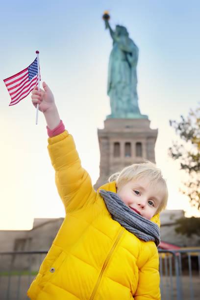 Niño con bandera americana en el fondo de la estatua de la libertad en la misma pose. Viajar con niños. - foto de stock
