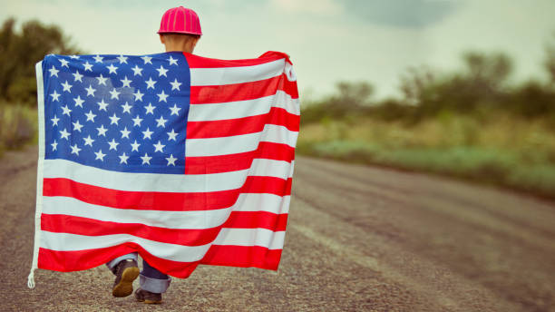 Little boy with American flag Little boy waving with American flag walking on the road family 4th of july stock pictures, royalty-free photos & images