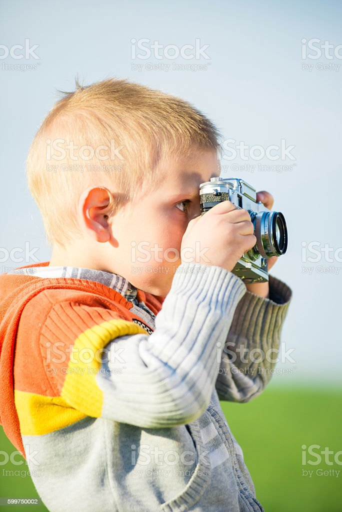 Little boy with an old camera shooting outdoor. stock photo