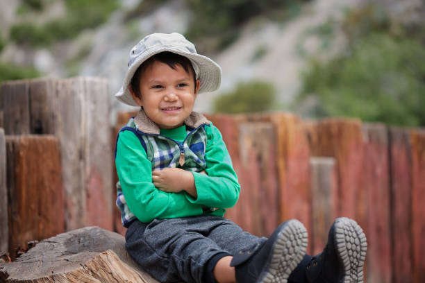 Little boy with arms crossed and sitting, waiting at the trailhead wearing his hiking boots and hat. stock photo