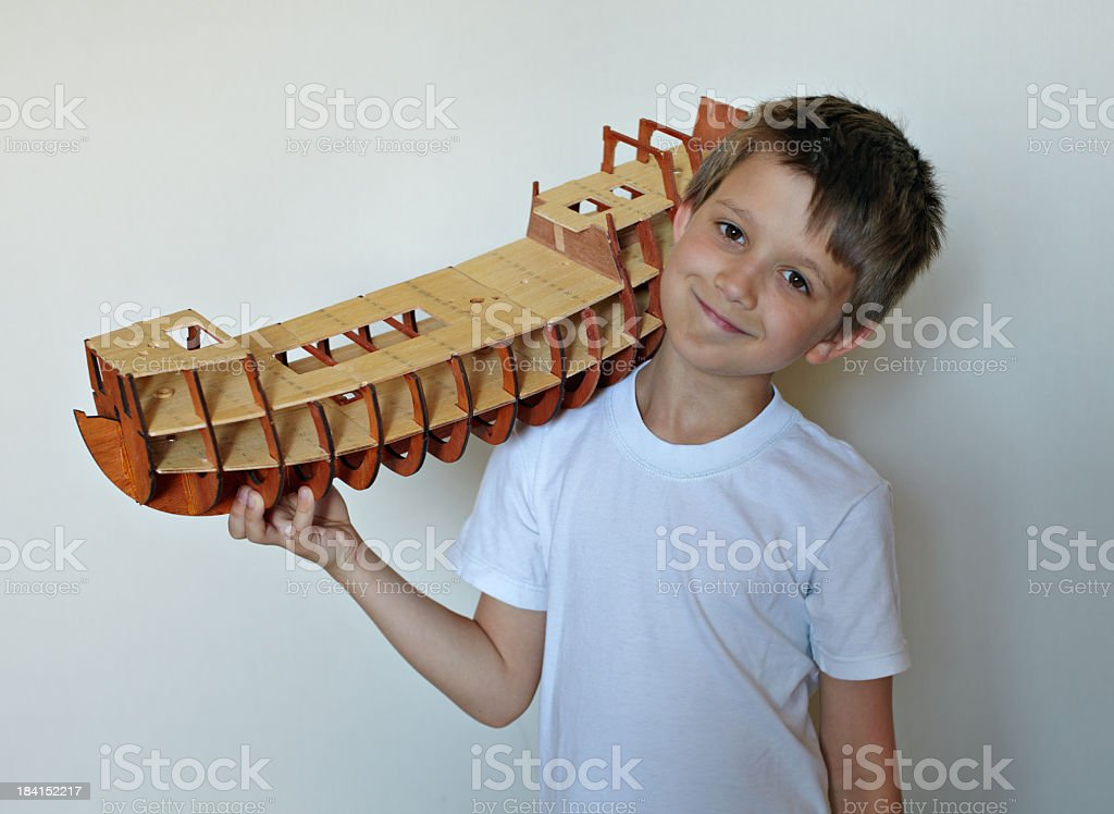 Little boy with artificial model of an ancient ship stock photo