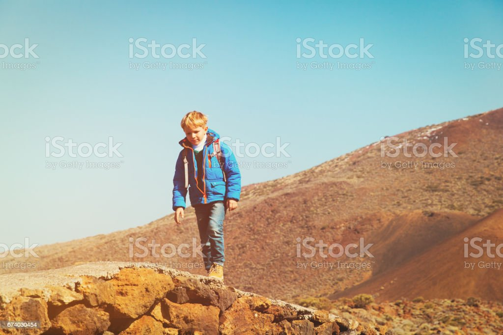little boy with backpack hiking in mountains royalty-free stock photo