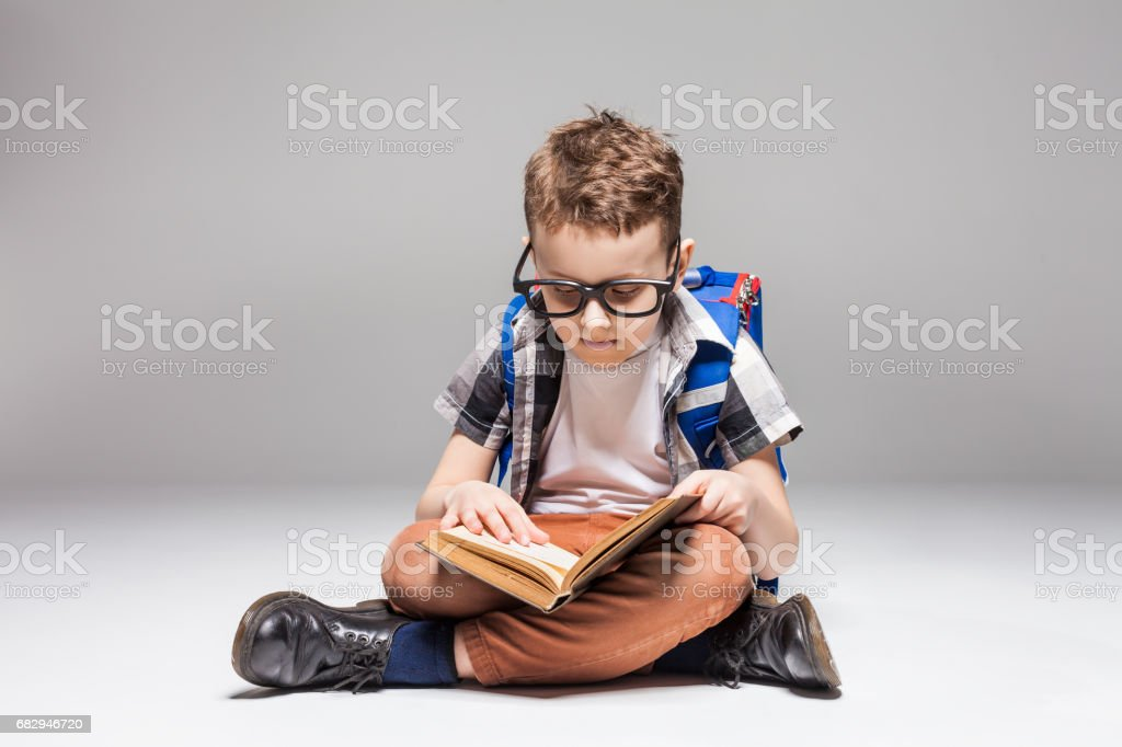 Little boy with backpack reading book in yoga pose royalty-free stock photo