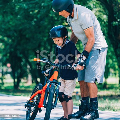 853720192 istock photo Little boy with bicycle, getting help from his grandpa 615421440