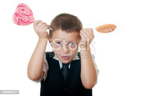 istock Little boy with big candy on white background 465954277