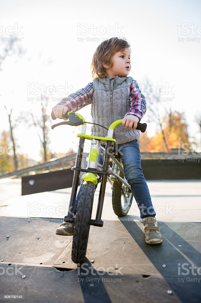 Little boy with bike on sports ramp at skate park. stock photo