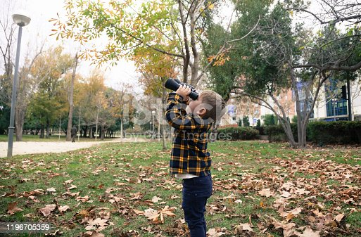 Little boy with binoculars exploring forest in autumn
