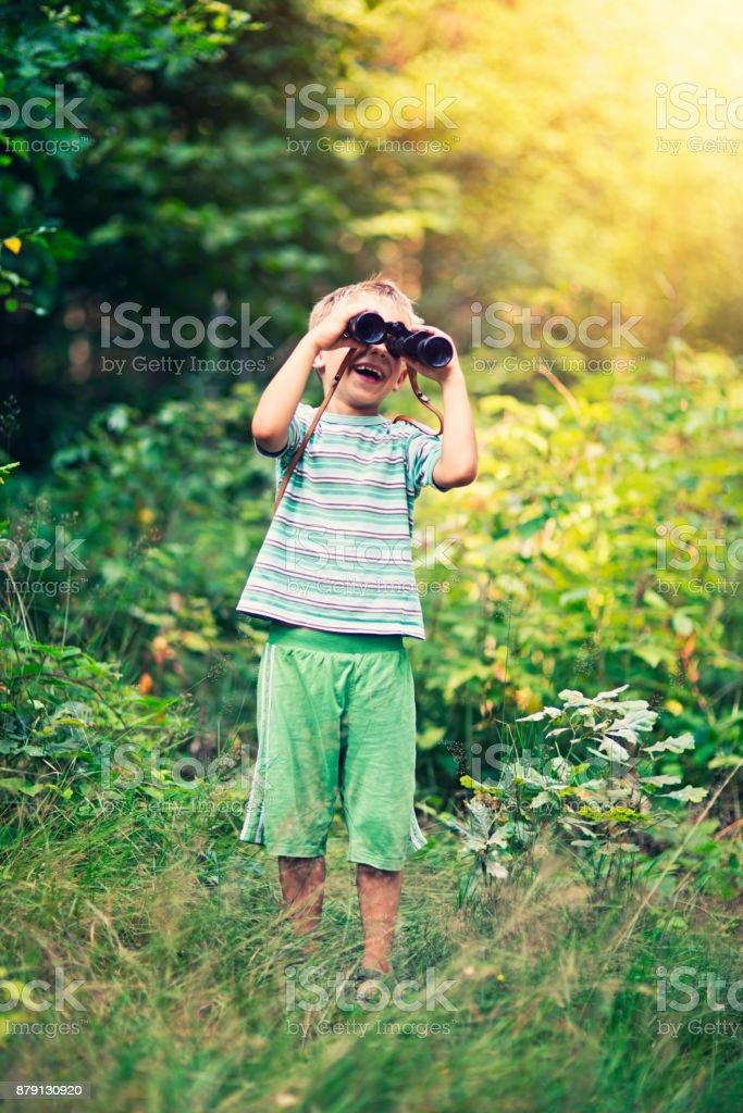 Kleiner Junge mit Fernglas erkunden Wald im Sommer – Foto