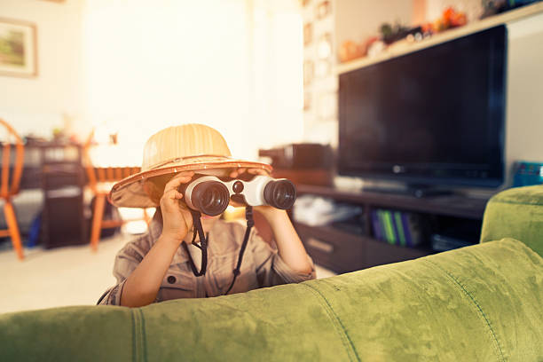 little boy with binoculars exploring living room - binocular boy bildbanksfoton och bilder