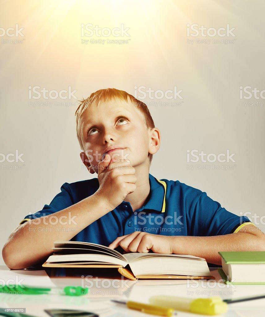 Little boy with book looks up toward inspiring light stock photo