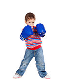 Little boy standing with blue boxing gloves, isolated on white
