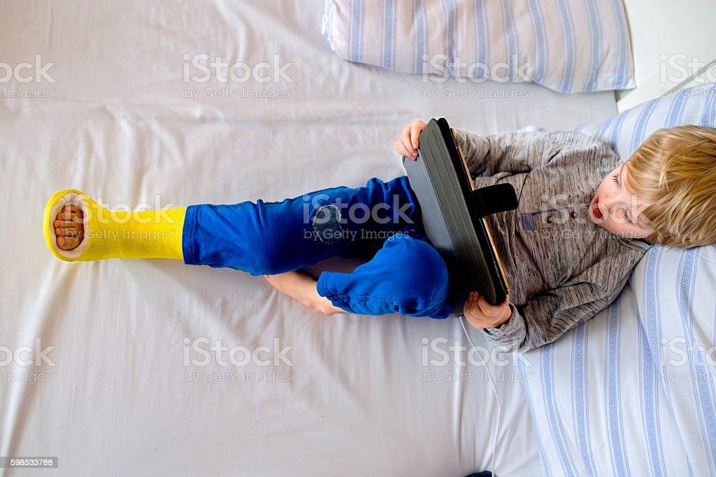 Little boy with broken leg playing on tablet photo libre de droits