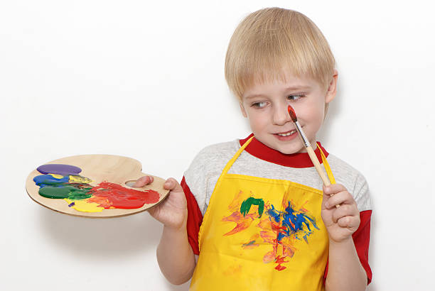 Little boy with brush and Artist's palette stock photo