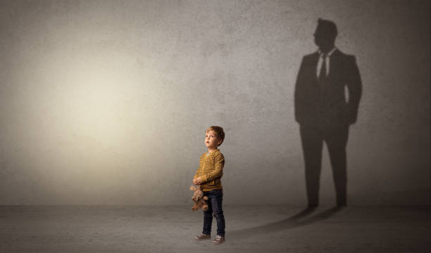 Little boy with businessman shadow stock photo