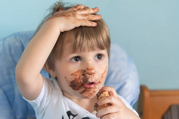Little boy with chocolate ice cream smeared on face. Little boy eating ice cream stock photo