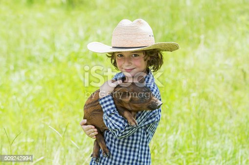 Little boy, 6 years old, wearing a cowboy hat and carrying a baby pig, smiling and looking at the camera. He is standing in a bright, sunny field.